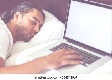 freelancer man with laptop in the morning in his bed emotionally talks at work, free schedule, happy business