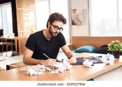 Freelancer man in t-shirt drawing with pencil on paper sitting at desk.