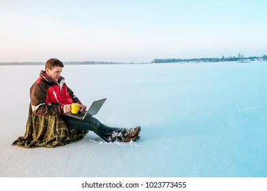 A freelancer man in warm jacket works with a laptop on the surface of a frozen lake. Toned.
