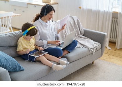 Freelancer mother sitting on couch at home office during lockdown, remote work on laptop. Child using tablet, playing in game at tablet, sitting with mom on sofa. Family, telework, e-learning concept.