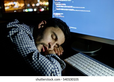 Freelancer programmer falling his face down taking a nap with computer. Concept of tired and lazy