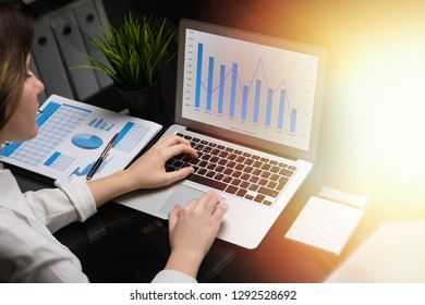 Freelancer typing on laptop with blank black screen next charts and calculator