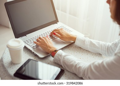 Freelancer using notebook, woman working on laptop computer typing on the keyboard at home.