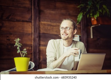 Freelancer working, drinking tea, looking aside. Man at home working looking in window, holding cup.