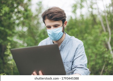 Freelancer working during the quarantine outdoors in the woods or in the park. Stylish young man in a mask and with a laptop outside