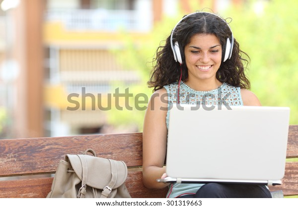 Freelancer working with a laptop and headphones sitting on a bench in a park