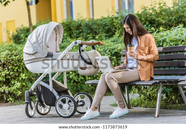 freelancer working with laptop on bench near baby stroller in park and holding coffee in paper cup