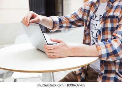 Freelancer working with netbook in the city. Young man in checkered shirt doing remote work on the city street.