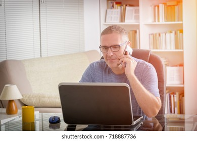 Freelancer working on laptop computer while talking on the smart-phone at home or office