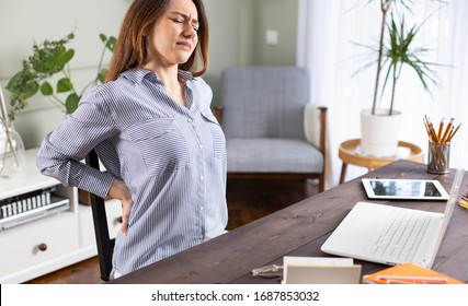 Freiberufliche junge Frau mit Rückenschmerzen während ihrer Arbeit zu Hause