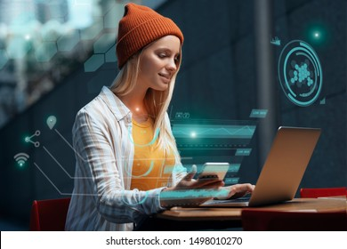Freelancers of the future could be working with a digital HUD around them. A millennial young woman is working with her laptop and phone in a cafe, while a holographic projection encircles her.