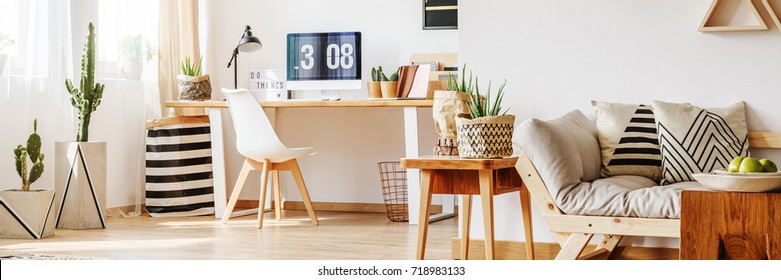 Freelancer's workspace with cacti and patterned pillows on beige sofa in multifunctional living room