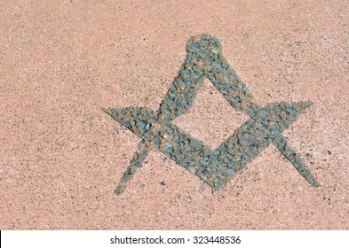 Freemasonry symbol made from stones on the ground.