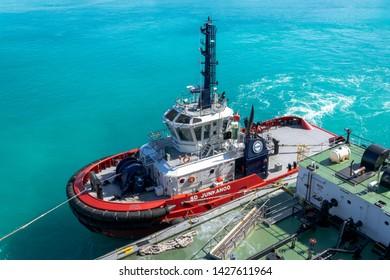 """Freeport, Bahamas - May 2019: Tug boat SD Junkanoo assisting a refueling barge at the cruise port in Freeport, Bahamas."""