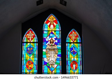Freeport, Grand Bahama, Bahamas- August 10, 2019: Stained glass windows in a Christian church. The beautiful glass depicts Jesus Christ in the center and other religious symbols in both sides