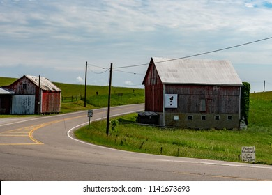 Freeport, Ohio/USA: June 9, 2018: Many rural routes in Appalachia follow old wagon trails and cut right through the middle of farms. Here barns are on opposite sides of the road.