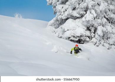 Freeride skiier riding in deep powder snow