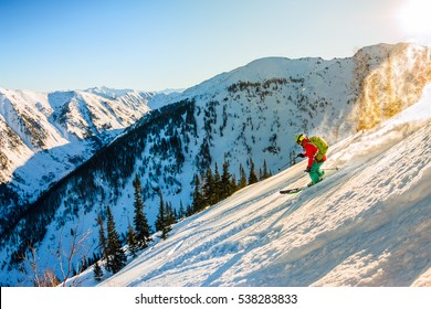 Freerider skier descends from the mountain in the light of the morning sun