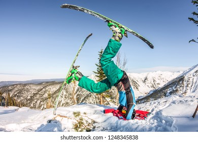 Freerider skier doing yoga stands on his head in skiing in the snowy mountains