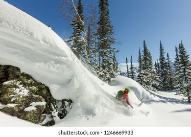 Freerider skier jumps from a rock of snow in trees in the mountains
