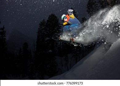 freerider snowboarder jumping at night with a springboard in the forest.