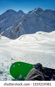 Freerider snowboarder sitting resting on track at background of beautiful Caucasian mountains on the winter resort