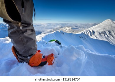 Freerider snowboarder standing on the hillside, prepared to descend on background of beautiful Caucasus mountains on winter resort