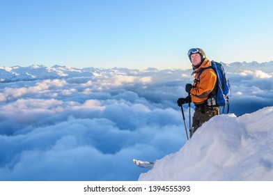 Freerider standing in high alpine region, enjoying the fantastic view over the clouds in the alps near Innsbruck