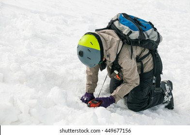 Freerider using an avalanche beacon to find a person buried by an avalanche