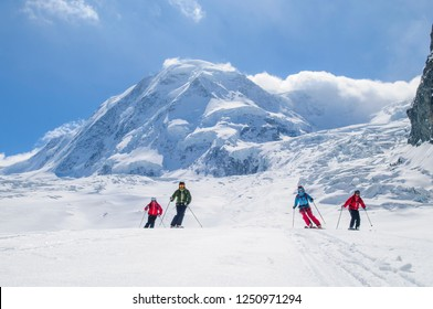Freeriders skiing in front of the impressive Monte Rosa