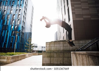 Freerunner is doing a backflip off a wall in the city.