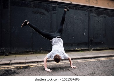 Freerunner is doing a cartwheel in the street.