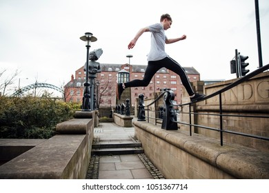 Freerunner is jumping between walls and railings in the city.
