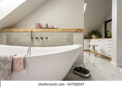 Freestanding bath with towels in grey modern bathroom