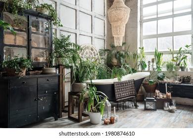 Freestehende klassische Badewanne mit hängendem Handtuch in hellgemütlichem, schicken Badezimmer mit viel Grün und antiken Möbeln, schwarzer Vintage-Schrank mit Topfpflanzen und Kerzen auf Holzfußboden