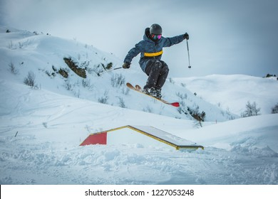 Freestyle Skier jumping over a box in a snow fun park