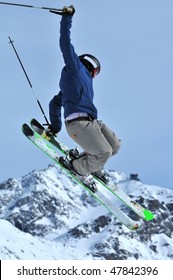 a freestyle skier touches his skis during a jump