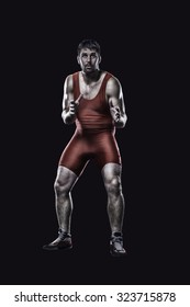 Freestyle wrestler in red uniform in ready position isolated on black background