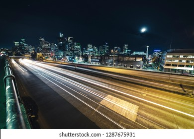 Freeway Cityscape of Car Streaks and Seattle Skyline Building Lights Under Moon