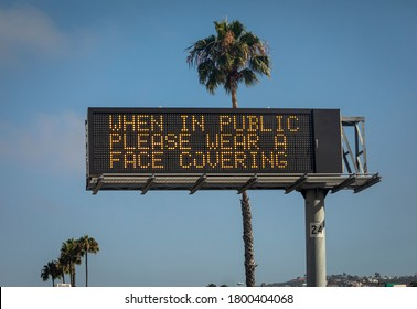 Freeway sign stating When in Public Please Wear a Face Covering . Palm trees are in the background against a blue sky