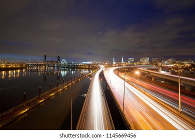 Freeway traffic light trails along Willamette River with city of Portland Oregon skyline at night