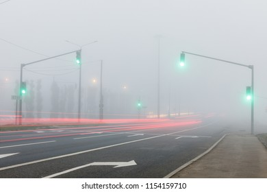 Freeway, traffic lights and tracks of car lights in fog at early morning.