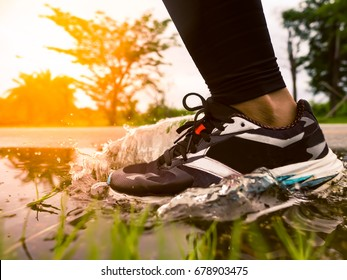 Freeze action of athlete's legs and running shoes splashing water after heavy rain, nature and sunset background, show water droplets