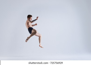 Freeze action shot of flying shirtless and barefooted young male boxer wearing trunks jumping high against blank grey studio wall background with copy space for your advertising information.