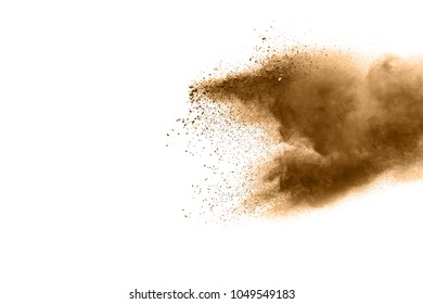 Freeze motion of brown dust explosion. Stopping the movement of brown powder. Explosive brown powder on white background. Dry soil splater on white background.