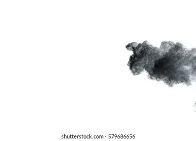 Freeze motion explosion of  black dust on white background. By throwing talcum powder out of hand. Stopping the movement of black powder on dark background.