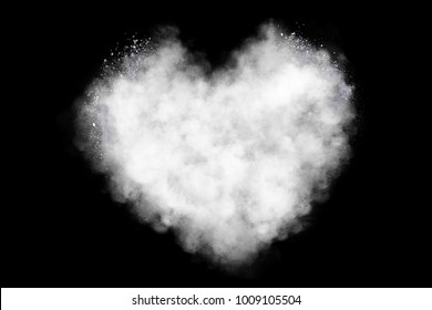 Freeze motion of heart shaped powder isolated on black background. Abstract design of dust cloud. Particles explosion screen saver, wallpaper with copy space. Love, passion, feelings concept