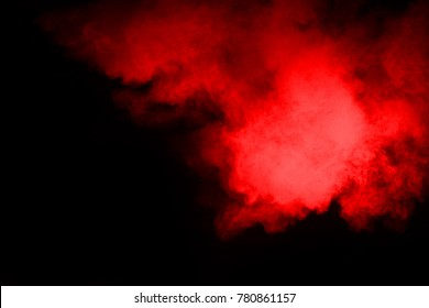 Freeze motion of red powder exploding, isolated on black background. Abstract design of red dust cloud.
