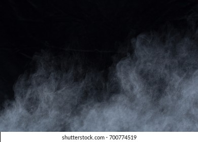 Freeze motion of white dust explosion on black background. Stopping the movement of white powder on dark background. Explosive powder white on black background.