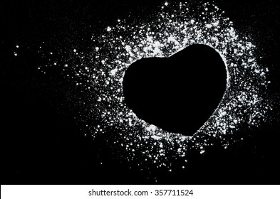 Freeze motion of white powder on black dark background. Abstract design of dust cloud. Particles heart shaped explosion screensaver, wallpaper with copy space. Love, passion, care concept